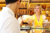 Baker's shop shopkeeper gives bread to customer — Stock Photo