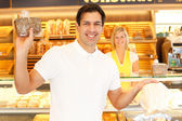 Happy customer in bakery with bags of bread — Stock Photo