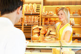 Shopkeeper with basket of bread — Stock Photo