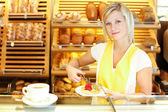 Shopkeeper in baker's shop preparing coffee and cake — Stock Photo