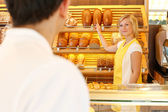 Shopkeeper in baker's shop with customer — Stock Photo