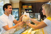 Shopkeeper giving pastry to customer — Stock Photo