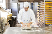 Baker kneading dough in bakery — Stockfoto