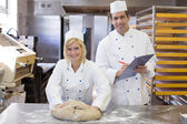 Instructor instructing an apprentice in bakery — Stock Photo