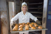 Baker in bakehouse or bakery putting bread in the oven — Stock Photo