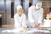 Baker instruction apprentice in kneading bread dough — Stock Photo