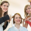 Hairdressers cutting customers hair in salon - Stock Photo