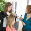 Apprentice cutting hair while instructor is watching — Stock Photo