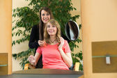 Hairstylist shows client her new haircut — Stock Photo