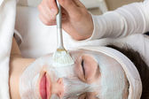Cosmetician giving client facial skincare mask — Stock Photo