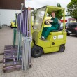 Stock Photo: Glazier operating forklift truck with panes of glass