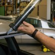 Glazier using application gun to apply adhesive for windscreen — Stock Photo