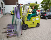 Glazier operating a forklift truck with panes of glass — Stock Photo