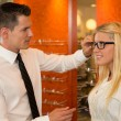 Optician or optometrist consulting a customer about eyeglasses — Stock Photo