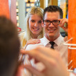 Stock Photo: Couple in optician's shop trying spectacle frame
