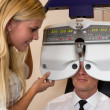 Stock Photo: Optician or optometrist and patient with a phoropter