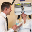 Optician or optometrist and patient with a phoropter — Stock Photo