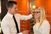 Optician or optometrist consulting a customer about eyeglasses — Foto de Stock