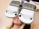Customer of a optometrist or optician looking through phoropter — Stock Photo