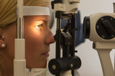 Patient at slit lamp of optician or optometrist — Stock Photo