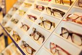 Eyeglasses, shades and sunglasses in optometrist's shop — Stock Photo