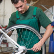 Mechanic repairing wheel on a bicycle in workshop — Stock Photo