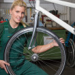 Bicycle mechanic repairing wheel on bike in a workshop — Stock Photo