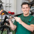 Bicycle mechanic carrying a bike in workshop — Stock Photo