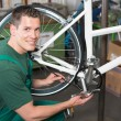 Bicycle mechanic repairing tooth belt in a workshop — Stock Photo
