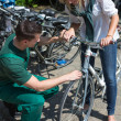 Bicycle mechanic in bike shop consulting a customer — Stock Photo