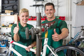 Bicycle mechanic and apprentice repairing a bike — Stock Photo