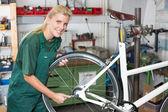 Bicycle mechanic repairing wheel on bike — Stock Photo