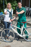 Bicycle mechanic and customer in bike store giving thumbs up — Stock Photo