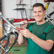Bicycle mechanic carrying a bike in workshop smiling — Stock Photo
