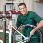 Mechanic repairing wheel on a bicycle in workshop — Stock Photo