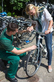 Bicycle mechanic in bike shop consulting a customer — Foto de Stock