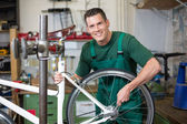 Mechanic repairing wheel on a bicycle in workshop — 图库照片