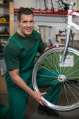 Fiets mechanic herstellen wiel op fiets in een workshop — Stockfoto