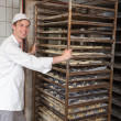 Baker pushing rack full of bread into the oven — 图库照片