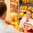 Saleswoman in bakery selling bread to customer — Stock Photo