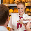 Saleswomin baker's shop selling bread to customer — Stock Photo #28642559