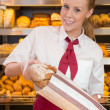 Shopkeeper in baker's shop selling bread to customer — Foto Stock