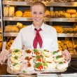 Saleswoman in bakery presenting sandwiches to customer — ストック写真