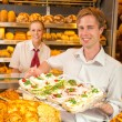 Buyer in bakery presenting tray with sandwiches — Stock Photo