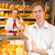 Customer holding a pretzel in baker's shop — Stock Photo