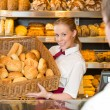 Baker in bakery with basket full of bread — Stock Photo