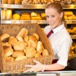 Shopkeeper in baker's shop presenting buns in a basket — Photo