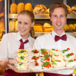 Two bakers holding tray with sandwiches in baker's shop — Stock Photo