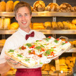 Shopkeeper in baker's shop with tablet of sandwiches — Stock Photo