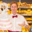 Baker with wedding cake in confectionery — Stock Photo